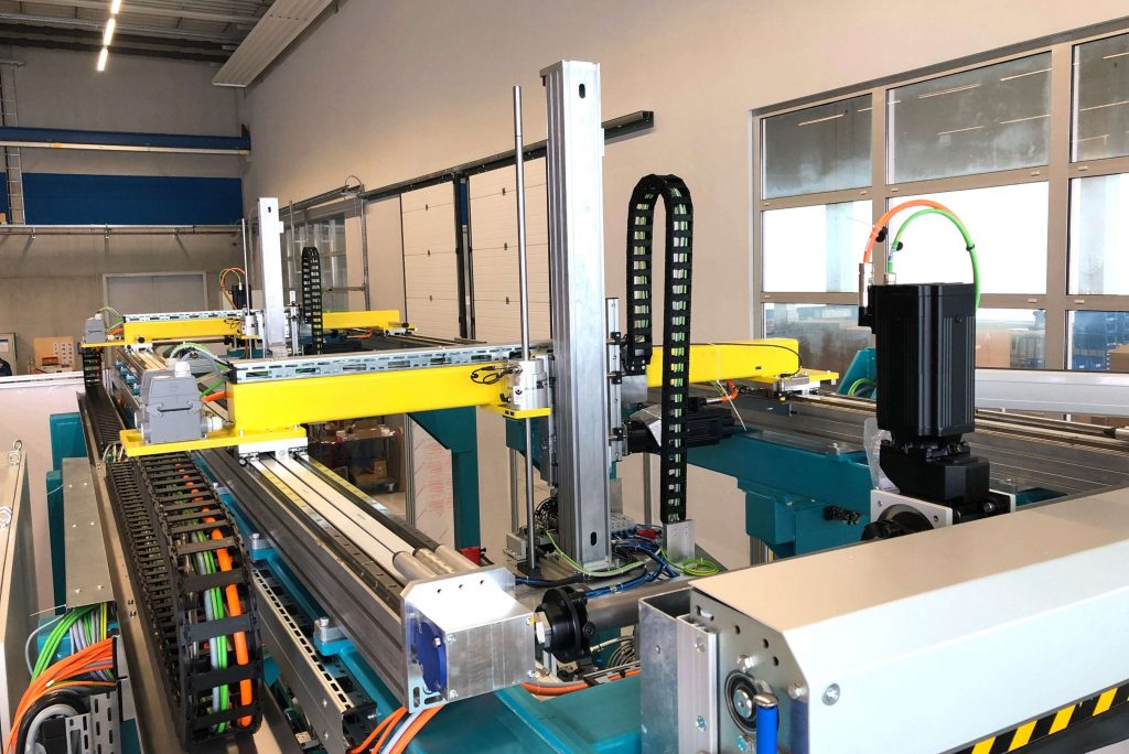 Die Portaleinheit der neuen Montagelinie schleust die Gehäusebleche durch den Prozess und führt sie präzise an je zwei Nietaggregate heran.