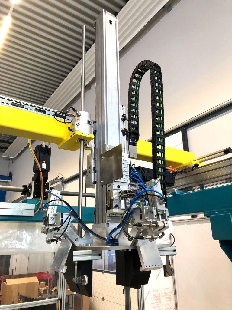 Die Metallblechgehäuse werden in Hebe/Greifer-Aufnahmen fixiert, die vertikal und horizontal verfahrbar sind.