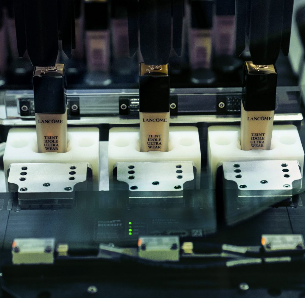 Vor der Abfüllung setzt ein Handlingroboter die leeren Behälter in zum Produktformat passende Pucks (Transportbehälter) ein, die an den Movern des XTS befestigt sind.