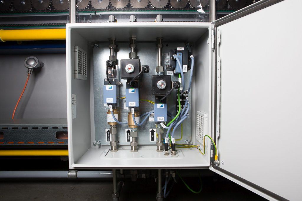 Rollenherdofen für das Presshärteverfahren hochfester Stähle. In jedem derSchaltschränke sind zur Regelung der Gaszufuhr drei Massendurchflussregler integriert. Eine Steuereinheit kommuniziert über Profinet mit der übergeordneten Ofen-SPS, die die Prozesswerte verwaltet und den Prozessablauf dokumentiert.