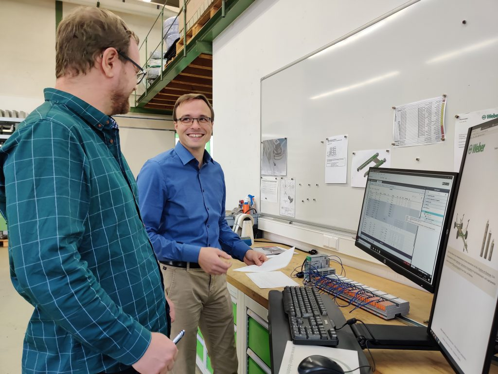 Geschäftsführer Maximilian Weber (hinten) und seinen Mitarbeiter Tobias Feindler hat die komfortable Programmerzeugung in der Engineering-Umgebung PLCnext Engineer überzeugt.
